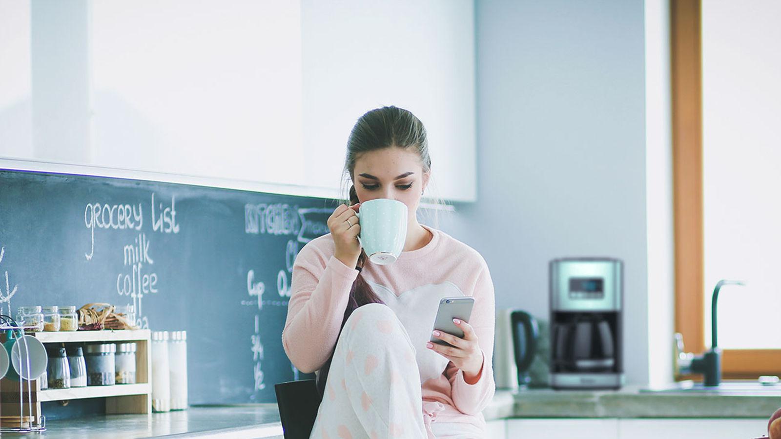 Kahve içen teknoloji ile ilgili bir kadın